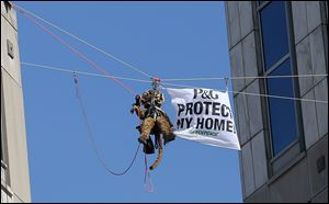 Greenpeace activists, including this one dressed in a tiger suit, rappel and hang banners in protest of Procter & Gamble outside of the company's headquarters, in downtown Cincinnati, Tuesday.
