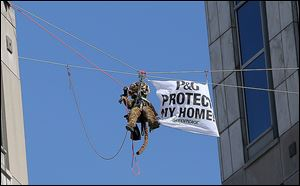 Greenpeace activists hang banners from Procter & Gamble headquarters in Cincinnati to protest the company's use of palm oil from a supplier that Greenpeace linked to forest destruction.