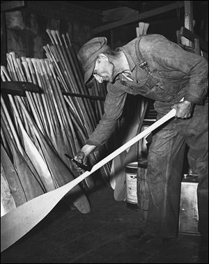 Otto Brodbeck  varnishes paddles in this 1949 photo.
