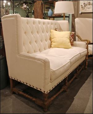 A tufted high back settee with exposed wood legs and stretchers is from the Donny Osmond Home Collection.