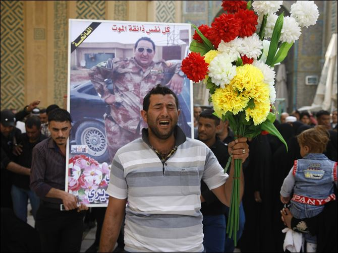 Ghaith Ismail, center, holds flowers during the funeral procession for his brother, Layth Ismail, on Thursday in the Shiite holy city of Najaf, 100 miles south of Baghdad, Iraq.