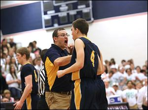 Toledo Christian's head coach David McWhinnie cheers his player, junior Matthew Brumbaugh (4) in a timeout during the third quarter.
