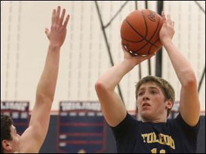Toledo Christian's junior Kyle Kempton (11) puts up two points over Ottawa Hills' junior Nick Hauck (20) during the third quarter.