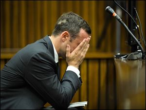 Oscar Pistorius, cradles his head in his hands in court on the fifth day of his trial at the high court in Pretoria, South Africa. The Olympian is charged with murder for the shooting death of his girlfriend,  Reeva Steenkamp, on Valentines Day in 2013.