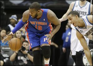Detroit Pistons' Greg Monroe, left, reaches for the ball as Minnesota Timberwolves' Kevin Martin rushes in during the first quarter.