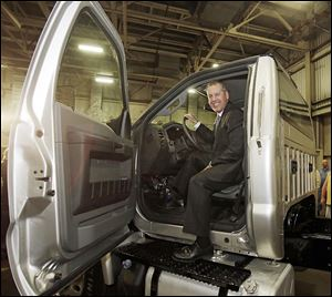 Joe Hinrichs, Ford's president of the Americas, sits behind the wheel of a Ford F-750 medium-duty truck at the Ohio Assembly Plant on Friday in Avon Lake, Ohio, where one of two new truck models will be produced starting in 2015.