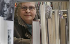 Bowling Green resident Barb Bertonaschi poses with books at the Wood County Library in Bowling Green. It's been seven years since the 59-year-old woman had a paycheck. She's trying to take classes at Owens Community College, but education is expensive.