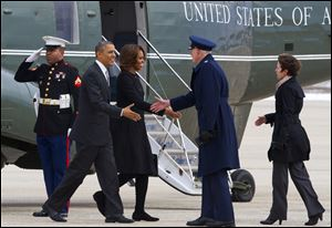 A Marine salutes as President Barack Obama and first lady Michelle Obama are greeted by 89th Airlift Wing Commander Col. David Almand and his wife Cathy Almand before boarding Air Force One for a trip to Florida.