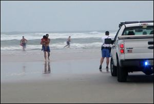 A lifeguard carries one of the three children rescued from a minivan that their mother, Ebony Wilkerson, drove into the Atlantic in Daytona Beach, Fla.