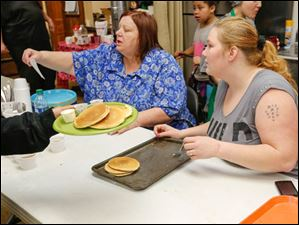Karen Peterson of Harbor View, left, and Angil Slover of Toledo serve pancakes. Slover is a volunteer from Christ United Methodist Church.