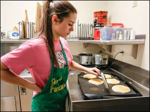 Megan Upham, 17, of Oregon flips pancakes. She is in the East Toledo YMCA Leadership Program.