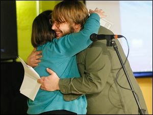 Organizer Ryan Bunch, right, gives Lucas County Commissioner Tina Skeldon Wozniak a hug after accepting a $500 check.
