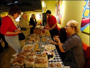 Stephanie Austin, right, helps customers by baked goods.