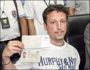 Luigi Maraldi of Italy shows his current passport at Phuket police station in Thailand. His old passport was used by a passenger aboard the missing airliner.