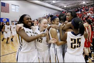 Notre Dame's Tierra Floyd (31) surrounded by teammates celebrate defeating Wadsworth 51-42 during the Division I girls basketball regional final.