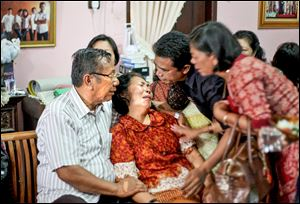 Family members comfort Chrisman Siregar, left, and his wife Herlina Panjaitan, the parents of Firman Siregar, one of the Indonesian citizens registered on the manifest to have boarded the Malaysia Airlines jetliner flight MH370 that went missing.