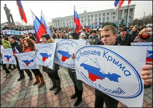 Pro-Russian supporters hold banners during a rally in Simferopol, Crimea. The protesters gathered in  Lenin Square on Sunday to urge a 'Yes' vote on the referendum next week on Crimea joining the Russian Federation.