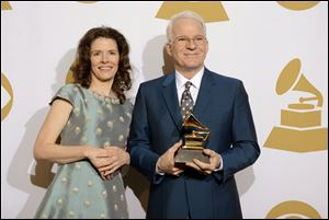 "Edie Brickell, left, and Steve Martin in the press room with the award for best American roots song, ""Love Has Come For You,"" at the January's Grammy Awards at Staples Center in Los Angeles."