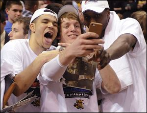 Wichita State's Ron Baker, center, takes a photo with Fred VanVleet, left, and Cleanthony Early after their victory over Indiana State in the championship game of the Missouri Valley Conference tournament Sunday in St. Louis.