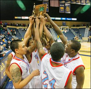 Bowsher High School players celebrate with their trophy after defeating St. John's Jesuit.