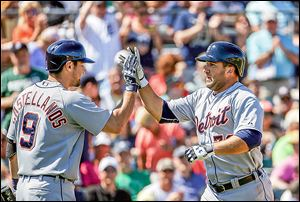 The Tigers' Tyler Collins, right, high-fives teammate Nick Castellanos after hitting a home run in the seventh inning.