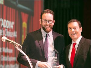 Bill Sattler of Madhouse Creative, left, accepts the Gold award presented to him by event host Jay Berschback o