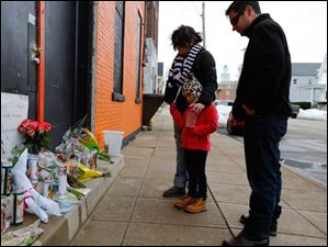 Dalena Buchman, left, her daughter Kyla Buchman, 5, and her husband Jeff Buchman at a memorial at the Last Call Bar on North Park Avenue.