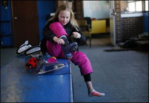 Sydney Mack, 9, takes off her skates at Ottawa Park ice rink on the last day of the season. With the city slashing the rink's budget by more than half from last year, the rink may not reopen in November.