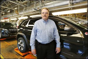 Chuck Padden, plant manager for the Toledo Assembly complex, stands in front of the line of completed Jeep Cherokees. The plant is currently assembling 990 Cherokees per day.