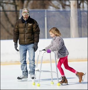 Dave Mack of Ottawa Hills watches as his daughter Emily Mack, 7, uses a walker to learn how to skate during an afternoon at the Ottawa Park ice rink. The season ended at the rink in West Toledo on Sunday.