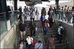 Pedestrians prepare to board a train at Union Station Friday in Los  Angeles.