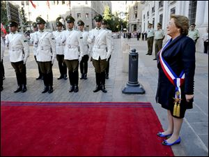 Chile's new President Michelle Bachelet reviews the troops as she arrives to Moneda presidential palace in Santiago, Chile.