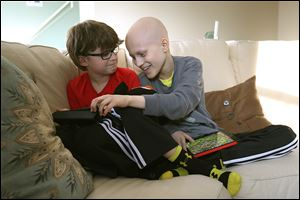 Gavin Boggs, right, jokes with his brother, Zachary, as they play a game on their iPads together at their home in Rossford.