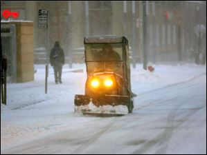 A plow clears Madison Avenue during a level 3 snow emergency in Toledo Wednesday.