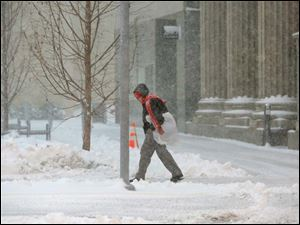 Rita Wheeler battles the snow and wind to make here way to work in downtown Toledo.