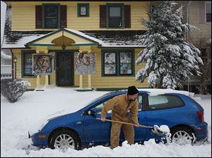 Peter Beck of West Toledo digs his car out of the snow on the street in front of his neighbors' house. Seven inches of snow was recorded at Toledo Express Airport.
