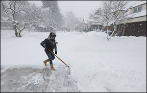 Wendy Hayes shovels snow at her Old Orchard home Wednesday. Area school districts have pondered how to make up a bevy of days missed because of snow.