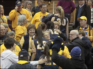 Toledo's women's basketball players are embraced by family, friends and fans in the stands after the game.