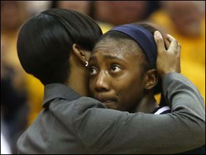 Toledo's Andola Dortch (22) is embraced by a member of coaching staff after the loss. Dortch scored 10 points, pulled down five rebounds and logged five steals in the game.