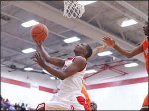 Bowsher High School player Dajuan King (13) drives to the basket against Mansfield Senior High School during the third quarter.