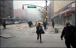 People run after an explosion and building collapse in the East Harlem neighborhood of New York, Wednesday.