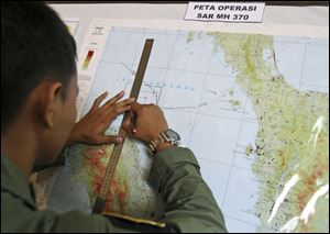 An Indonesian Air Force officer draws a flight pattern flown earlier in a search operation for the missing Malaysia Airlines Boeing 777, during a post-mission briefing at Suwondo air base in Medan, North Sumatra, Indonesia today.