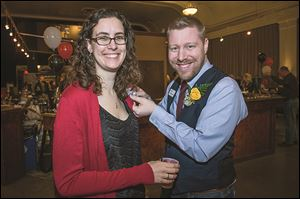 Jess Buetikofer gets a corsage pinned on by her husband Eric during the American Red Cross of Wood County's Fire & Ice event.