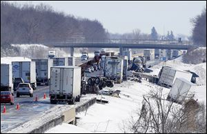 Crews clean the remains of a multivehicle accident in the eastbound lane of the Ohio Turnpike near the County Road 268 overpass near Clyde on Thursday. Three people died in a couple of chain-reaction wrecks.