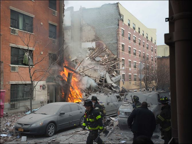 NYC Explosion Firefighters work the scene of an explosion and building collapse in the East Harlem. The explosion leveled an apartment building, and sent flames and billowing black smoke above the skyline.