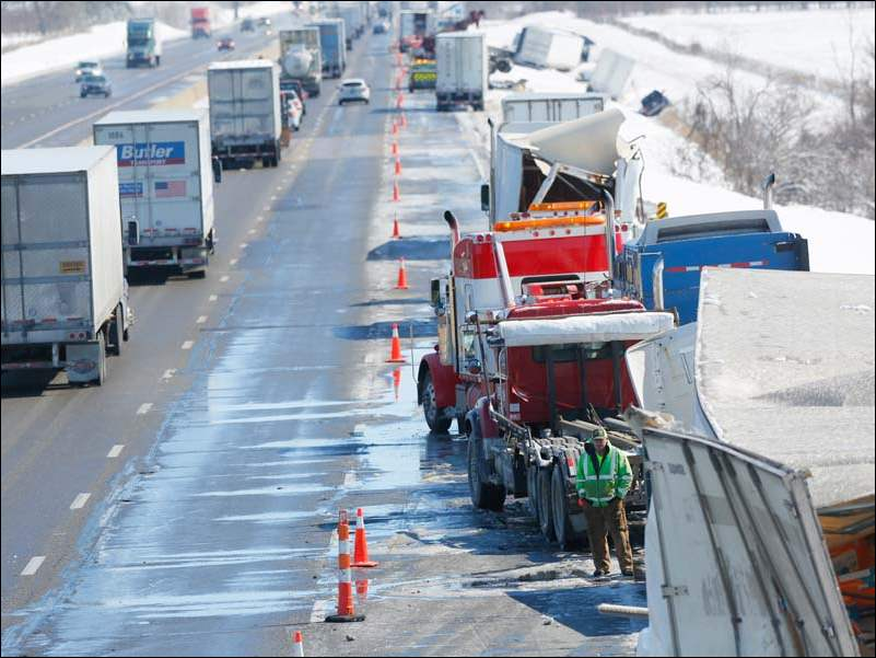 Traffic inches by while crews work to clean the remains of a multi-vehicle accident in the eastbound lane of the Ohio Turnpike near the County Road 268 overpass near Clyde Thursday.