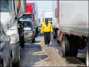 Paul Artison walks through backed-up traffic on on U.S. 20 eastbound near Hicksville.