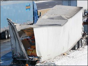 The damaged cargo of a truck sits along the eastbound lane of the Ohio Turnpike near Clyde.