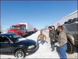 John Gooch, left, from South Carolina, Scott Krohn, center, from Fremont, and Corey Weiner, right, figure-out how to get Krohn's car off of a median while traffic is backed-up on U.S. 20 eastbound near Hicksville.