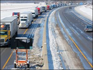 Traffic inches down the eastbound lane of the Ohio Turnpike near Clyde while crews work to clean the remains of Wednesday's multi-vehicle accident.